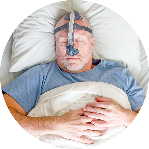A man laying in a hospital ward with a breathing apparatus